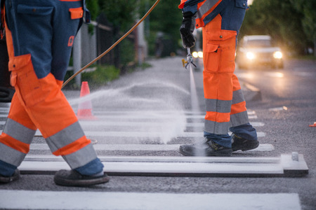 Traffic line painting. Workers are painting white street lines on pedestrian crossing. Road cones with orange and white stripes in background, standing on asphalt during road construction works Stockfoto