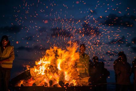 Groot brandend vuur met zacht gloeiende vlammen en rondvliegende sprankeltjes. Romantische zomeravond, mensen ontspannen en genieten van rust aan de kust tijdens de nacht van oude lichten Stockfoto - 97234726