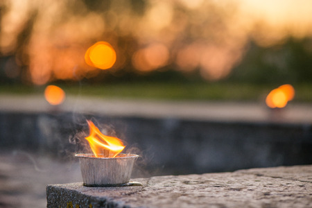 Macro shot of lit candle burning with soft glowing flame and smoke on romantic sunset background. Candle path at the park close to the seaside during the Night of ancient lights Stock Photo