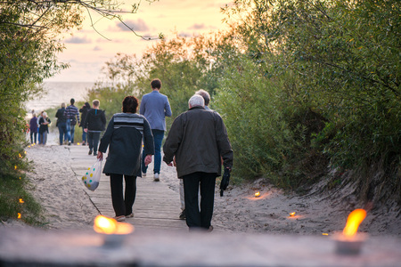 Romantic bonfire night at seaside during sunset. People gathering together to celebrate Night of ancient lights. Old couple walking on wooden pathway towards sea
