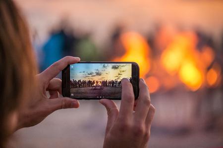 Vrouw neemt foto van zonsondergang met slimme telefoon. Romantische vreugdevuuravond aan zee. Mensen verzamelen zich om de nacht van oude lichten te vieren. Groot brandend kampvuur met zachte gloeiende vlam.