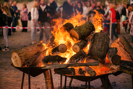 Large burning bonfire with soft glowing flame and sparkles flying all around. Romantic summer evening, people relaxing and enjoying calmness at the seaside during the Night of ancient lights.