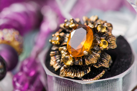 Macro shot of silver engagement ring in gift box on colorful, sparkling background. Ring made of yellow sapphire and citrine stone. Healing, natural crystals and powerful energy Banque d'images