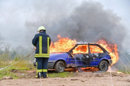 Fire fighter prepare to attack a propane fire. Burning and crashed car after explosion. Accident on street at countryside. No one was injured. Stock Photo
