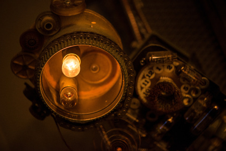 A bright, abstract, steam punk style bulb in the middle of the night hung on a ceiling and old phone with dial in the background
