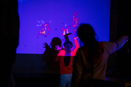 Abstract, blurry new technology background. Little girl is playing with interactive visual installation projected on wall Archivio Fotografico