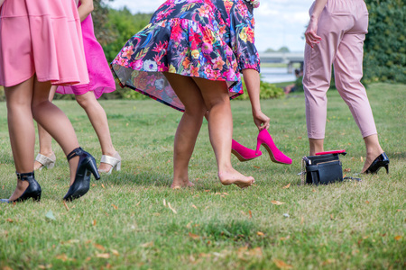 Girls wearing off high heel shoes in grass. Cheerful bride and bridesmaids party before wedding. Women having fun. Ladies purse, pink high heel shoes, smart phone left in grass. Girls freedom concept Stock Photo