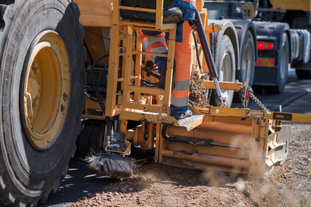 Road construction workers repairing highway road on sunny summer day. Loaders and trucks on newly made asphalt. Heavy machinery working on street. Road curbs being constructed with gravel Stock Photo