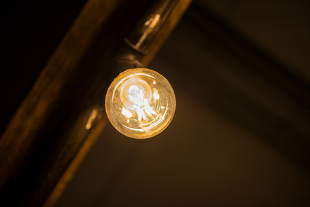 A bright bulb in the middle of the night hung on a ceiling Stock Photo