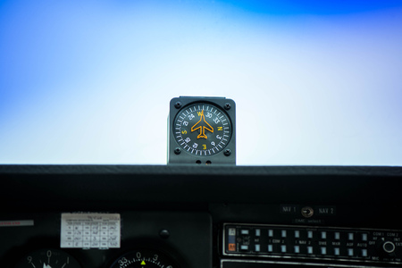 Macro shot of compass. Aircraft equipment, various indicators, buttons, instruments. The flight desk and control panel during take off and landing. Aircraft dashboard panel in pilot school