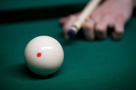 Sport billiard balls on green billiard table in pub. Player is about to hit the ball, focusing on his shot. On going billiard game. Competitive players trying to find out the winner of the round