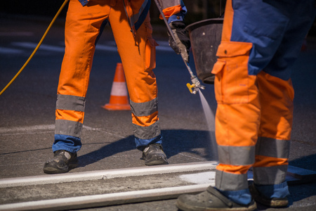 Traffic line painting. Workers are painting white street lines on pedestrian crossing.