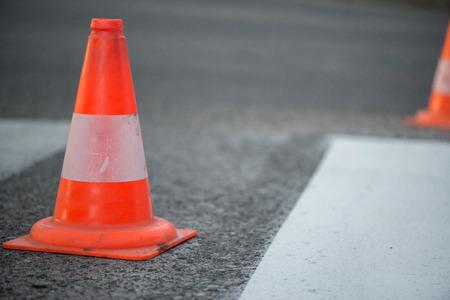 Colpo a macroistruzione di coni di traffico stradale con strisce arancioni e bianche in piedi sulla strada su asfalto grigio durante i lavori di costruzione di strade. Solo linee bianche dipinte su strisce pedonali Archivio Fotografico