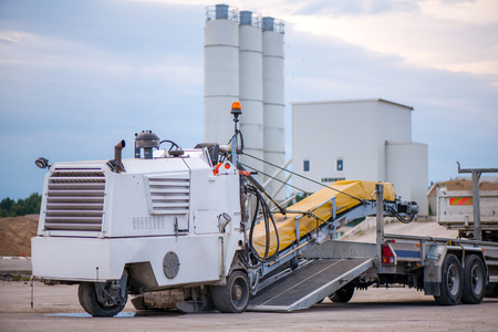 Cold milling machine being transported. Transportation trucks and construction machinery in large parking lot in industrial territory, next to concrete and asphalt factory