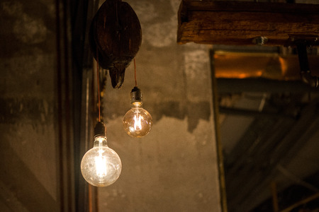A bright bulb in the middle of the night hung on a ceiling Stock Photo - 100360609