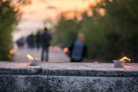Macro shot of lit candle burning with soft glowing flame and smoke on romantic sunset background. Candle path at the park close to the seaside during the Night of ancient lights 免版税图像