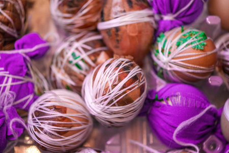 Easter eggs prepared for dyeing in onions peels, decorated with natural fresh leaves, plants, rice, colorful fabric and tied with white threads. Eggs laying in wicker wooden basket full of green grass