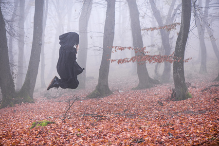 Girl in black hood is flying.  Run away from danger deep in dark forest. Thick fog all around. Scary autumn scene