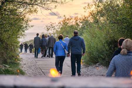 Romantic bonfire night at seaside during sunset. People gathering together to celebrate Night of ancient lights. Couple walking on wooden pathway towards sea