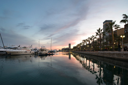 Beautiful port of Alicante, Spain at Mediterranean sea. Luxury yachts, ships, ferries and fishing boats sailing and standing in rows in harbor. Rich people traveling around the world. Sunset evening Stok Fotoğraf