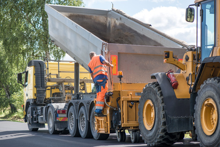 Road construction workers repairing highway road on sunny summer day. Loaders and trucks on newly made asphalt. Heavy machinery working on street. Road curbs being constructed with grave Stock Photo
