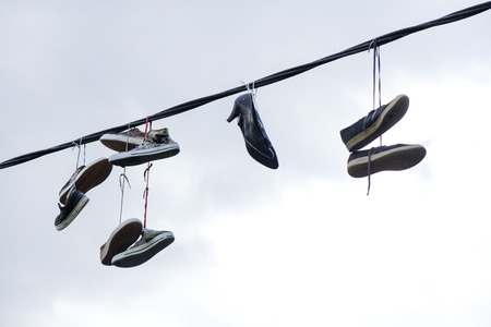 Old sneakers and high heel shoes hanging on electrical wire on overcast background