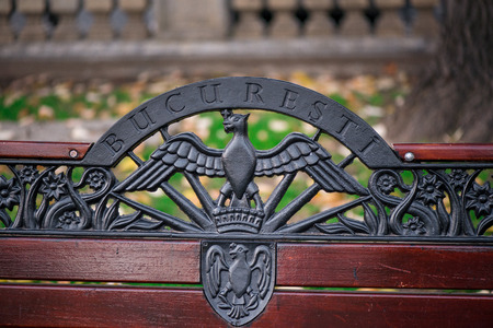 Wooden bench decorated with abstract ornaments in central park of Bucharest. (Bucuresti means Bucharest in english) Stock Photo