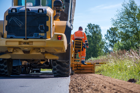 Road construction workers repairing highway road on sunny summer day. Loaders and trucks on newly made asphalt. Stock Photo