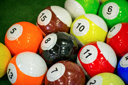 Shot of foot pool balls standing on green table. Foot Pool is the hybrid combination of pool and soccer. Big billiard balls.