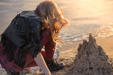 Young woman building and making sand castle next to sea. Calm, relaxing and romantic evening during sunset at the beach side. Remembering the childhood. Loneliness concept