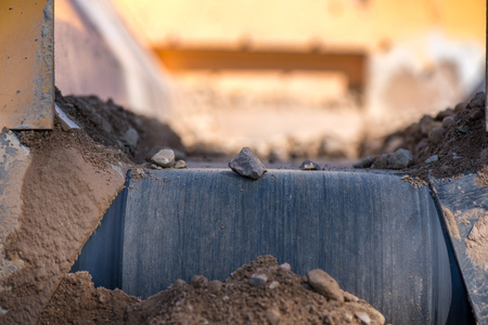 Rock filtering conveyor belt at a quarry. Pebbles and gravel falling out of a filtering facility onto a conveyor belt Stock Photo