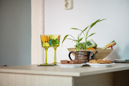 Good morning. Decorative hand painted glasses with flowers next to rustic, vintage pot for house plants, cookies on plates, tea and coffee standing on wooden table in kitchen. Archivio Fotografico