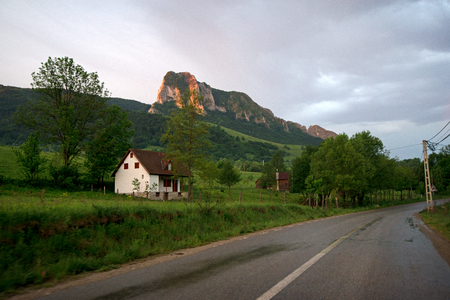 A village house built in front of a massive mountain. Early mourning sunrise shining over a mountain peak, where tourists climb a mountain.