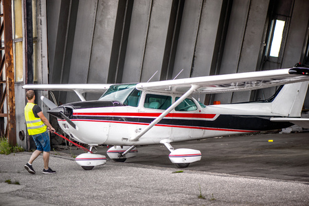 Single engine aircraft, ultra light plane ready for flight. Pilot is pulling out small motor air plane out from hangar in an old airport. Reklamní fotografie