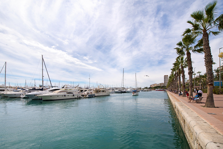 Beautiful port of Alicante, Spain at Mediterranean sea. Luxury yachts, ships, ferries and fishing boats sailing and standing in rows in harbor. Rich people traveling around the world. Sunny evening Stok Fotoğraf