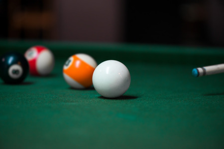 Sport billiard balls on green billiard table in pub. Player is about to hit the ball, focusing on his shot. On going billiard game. Competitive players trying to find out the winner of the round.