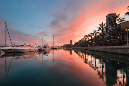 Beautiful port of Alicante, Spain at Mediterranean sea. Luxury yachts, ships, ferries and fishing boats sailing and standing in rows in harbor. Rich people traveling around the world. Sunset evening Foto de archivo