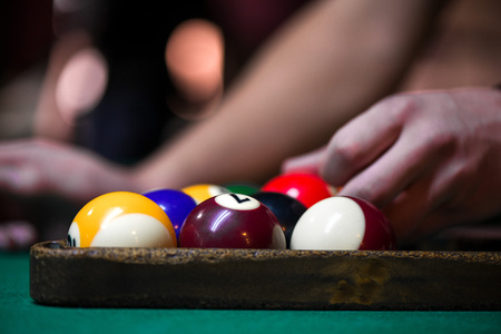 Sport billiard balls set arranged in shape of triangle on green billiard table in pub. Players are ready for the first hit of the round to start the billiard game. 스톡 콘텐츠