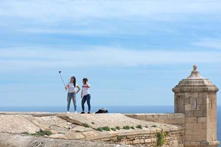 ALICANTE, SPAIN  march 29, 2018 : Two young girls standing on an edge of a fortress wall made of ancient stone and marble to take a self portrait with the view over a modern metropolitan city. Editorial