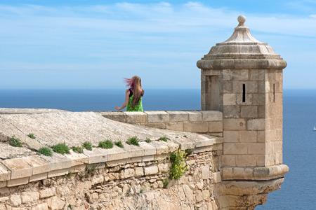 Young girl exploring ancient fortress built on top of mountains to protect kings from enemies. Strong wind blowing hair. Fortress stone wall around castle with small towers