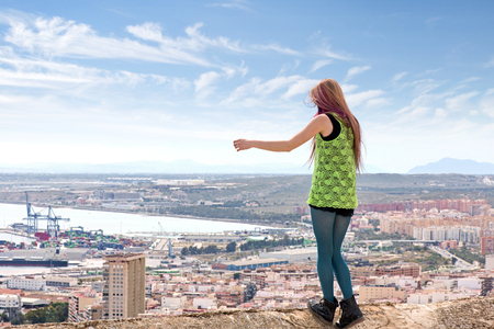 Young Caucasian girl standing on an edge of a Spanish conquistador fortress wall made of ancient stone and marble to enjoy the view over a modern metropolitan city. Girl ready to jump, suicide concept