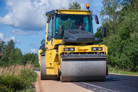 아스팔트 포장 도로에서 노란색 무거운 진동 롤러가 작동합니다. 도시에서 도로 수리. 화창한 여름 날에 고속도로로 수리 도로 건설 노동자. 중장비, 로더 및 트럭.