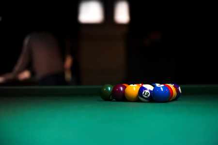 Sport billiard balls set arranged in shape of triangle on green billiard table in pub. Players are ready for the first hit of the round to start the billiard game