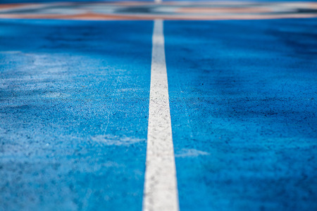 Abstract, blue background of newly made outdoor basketball court in park. Visible asphalt texture, freshly painted lines.