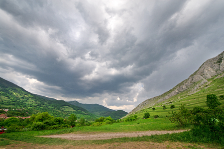 Sunny summer day, white clouds over mountain peak, where tourists climb to conquer fear, find courage and develop lateral thinking skills to overcome the difficulty of climbing a mountain. Small road Stock Photo
