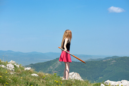 Young woman in pink skirts rotates hoop at the mountain top on beautiful nature background. Healthy lifestyle and love for fitness and sport. Freedom and fresh air outdoors