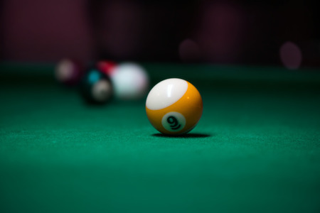 Sport billiard balls on green billiard table in pub. On going billiard game. Competitive players trying to find out the winner of the round