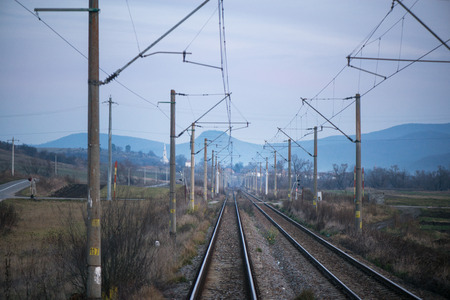 Eastern European railroad across Transilvania. Mountain landscape in the background. Scary, dangerous scene in winter with naked trees and polluted nature
