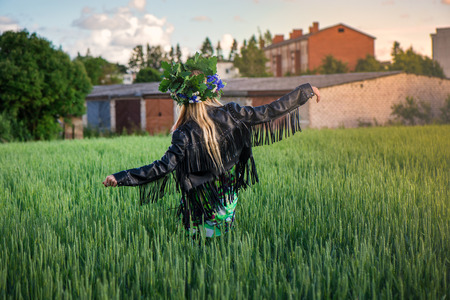 Beautiful girl with blonde hair, leather jacket and flower crown walking in meadow during sunset. Romantic, relaxing nature. Concept of recreation, meditation, spiritual healing and freedom.