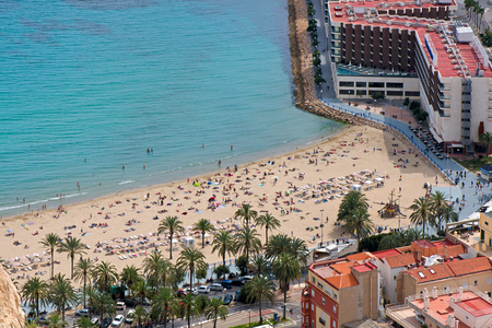 Panoramic view of Postiguet beach from Santa Barbara Castle in Alicante, Spain. Sunny day at Mediterranean sea. Block apartment buildings in a row. Palm trees and vibrant blue water.